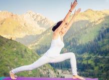 Εμπνευσμένη ασιατική γυναίκα που κάνει την άσκηση της γιόγκας στη σειρά βουνών Στοκ Φωτογραφίες