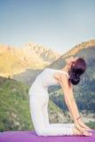 Εμπνευσμένη ασιατική γυναίκα που κάνει την άσκηση της γιόγκας στη σειρά βουνών Στοκ Φωτογραφία