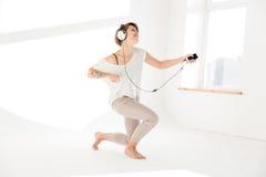Εμπνευσμένη γυναίκα που ακούει τη μουσική και που μιμείται παίζοντας την κιθάρα Στοκ Εικόνα