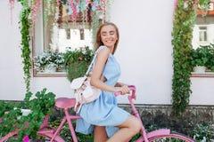 Εμπνευσμένη εύμορφη γυναίκα που στέκεται στο υπόβαθρο με το ρόδινο ποδήλατο στο μπλε φόρεμα Τρόπος ζωής έννοιας στοκ φωτογραφίες με δικαίωμα ελεύθερης χρήσης
