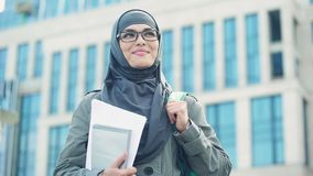 Εμπνευσμένη νέα γυναίκα σπουδαστής που φορά hijab το χαμόγελο, που στέκεται υπαίθρια στην πανεπιστημιούπολη απόθεμα βίντεο