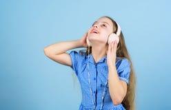 Εμπνευσμένος από τη μουσική Μουσική ακούσματος παιδάκι Χαριτωμένο παιδί με το μπλε υπόβαθρο ακουστικών Μικρό κορίτσι που φορά το  στοκ φωτογραφία