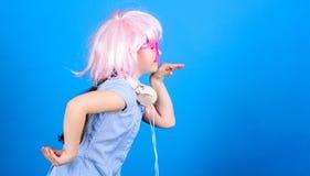 Εμπνευσμένος από τη μουσική Μουσική ακούσματος παιδάκι Χαριτωμένο παιδί με το μπλε υπόβαθρο ακουστικών Μικρή ρόδινη περούκα ακουσ στοκ φωτογραφίες