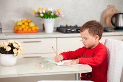 Εμπνευσμένος από το αγόρι επισύρει την προσοχή μια εικόνα σε χαρτί στον πίνακα στοκ φωτογραφία με δικαίωμα ελεύθερης χρήσης