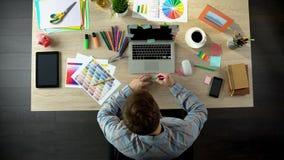 Εμπνευσμένος αρσενικός δημιουργός που γράφει κάτω όλες τις ιδέες του σχετικά με το κομμάτι χαρτί που θυμάται στοκ εικόνα