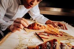 Εμπνευσμένος αρτοποιός που διακοσμεί τα ξύλινα πιάτα με τα επιδόρπια στοκ φωτογραφία με δικαίωμα ελεύθερης χρήσης