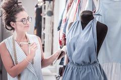Εμπνευσμένος βοηθός μόδας που φορά τα γυαλιά που αισθάνονται τα σοβαρά νέα jumpsuits προσαρμογής στοκ φωτογραφία