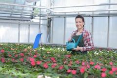 Εμπνευσμένος χαμογελώντας ανθοκόμος γυναικών με τα λουλούδια στοκ εικόνες