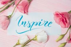 Εμπνεύστε το κείμενο Πηγή της κινητήριας λέξης εγγραφής στον άσπρο καμβά με το μπλε μελάνι Πλαίσιο eustoma λουλουδιών στο ρόδινο  στοκ φωτογραφίες με δικαίωμα ελεύθερης χρήσης