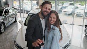 Εμπορία αυτοκινήτων επίσκεψης Το όμορφο ζεύγος κρατά ένα κλειδί του νέου αυτοκινήτου τους, της εξέτασης τη κάμερα και του χαμόγελ απόθεμα βίντεο