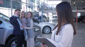 Εμπορία αυτοκινήτων, πορτρέτο της χαμογελώντας πωλήτριας υποβάθρου οικογένεια πελατών με την κόρη των ιδιοκτητών που αγοράζεται σ φιλμ μικρού μήκους