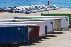 Εμπορευματοκιβώτια και νέα αυτοκίνητα που σταθμεύουν στο λιμένα Στοκ Φωτογραφία