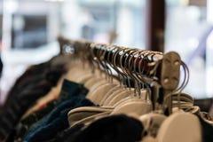 Εμπορικά ενδύματα που κρεμούν τη ράγα με τις κρεμάστρες παλτών και τα ενδύματα που κρεμούν κατά μήκος του πλήρους μήκους στοκ εικόνα