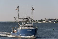 Εμπορικός δίκαιος αέρας αλιευτικών σκαφών με τα εργοστάσια του Νιού Μπέντφορτ στο υπόβαθρο στοκ εικόνα