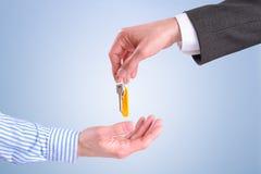 Εμπορικός πράκτορας που δίνει τα κλειδιά απομονωμένη στην πελάτης οριζόντια COM στοκ εικόνες