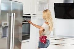 Εμπορικός χαριτωμένος μάγειρας κοριτσιών με το φούρνο στοκ φωτογραφία