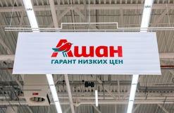 Εμπορικό σημάδι Auchan Κείμενο στα ρωσικά: Auchan - χαμηλή τιμή εγγύησης Στοκ Εικόνες
