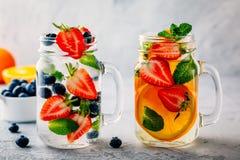 Εμποτισμένο detox νερό με το βακκίνιο, τη φράουλα, το πορτοκάλι και τη μέντα Πάγος - κρύα θερινή κοκτέιλ ή λεμονάδα Στοκ εικόνα με δικαίωμα ελεύθερης χρήσης