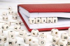 Εμπόριο λέξης που γράφεται στους ξύλινους φραγμούς στο σημειωματάριο άσπρο σε ξύλινο Στοκ φωτογραφία με δικαίωμα ελεύθερης χρήσης