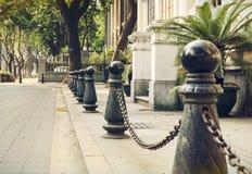 Εμπόδιο μετάλλων με την αλυσίδα σιδήρου στο πεζοδρόμιο οδών πόλεων από την άκρη του δρόμου Στοκ Φωτογραφία