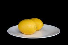 2 λεμόνια στο άσπρο πιάτο Στοκ Φωτογραφία