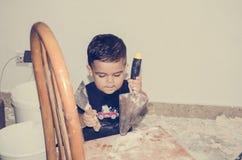 Ενάμισι χρονών παιχνίδι μωρών με τη ζωγραφική των εργαλείων στοκ φωτογραφία