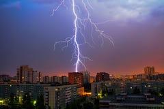ενάντια στην πόλη ανασκόπησης τα σκοτεινά θλιβερά σπίτια πλαισίων λάμψης άφησαν στην αστραπή δευτερεύον thunderstorm ουρανού Στοκ Εικόνα