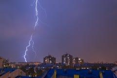 ενάντια στην πόλη ανασκόπησης τα σκοτεινά θλιβερά σπίτια πλαισίων λάμψης άφησαν στην αστραπή δευτερεύον thunderstorm ουρανού Στοκ Φωτογραφίες