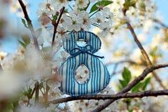 ενάντια στις λευκές κίτρινες νεολαίες άνοιξη λουλουδιών έννοιας ανασκόπησης Αριθμός 8 στα ανθίζοντας κεράσι-δέντρα Στοκ Εικόνες