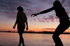 ενάντια στο περπάτημα ηλιοβασιλέματος σκιαγραφιών στοκ φωτογραφία με δικαίωμα ελεύθερης χρήσης