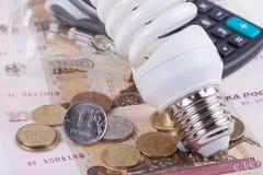 ενέργεια έννοιας - αποταμίευση Ηλεκτρική λάμπα φωτός, χρήματα ρουβλιών και υπολογιστής Στοκ Φωτογραφίες
