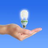 Ενέργεια - λαμπτήρας αποταμίευσης επάνω από το χέρι Στοκ Εικόνα