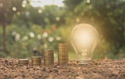 Ενέργεια - ανάπτυξη λαμπών φωτός και δέντρων αποταμίευσης στους σωρούς των νομισμάτων Στοκ Φωτογραφία
