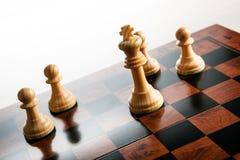 Ενέχυρα σκακιού σε μια σκακιέρα και ένα κομμάτι σκακιού του βασιλιά Στοκ φωτογραφία με δικαίωμα ελεύθερης χρήσης