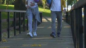 Ενήλικα άτομα που πηγαίνουν στο πάρκο για τις ασκήσεις πρωινού, καθημερινά τελετουργικά, υγιής τρόπος ζωής φιλμ μικρού μήκους