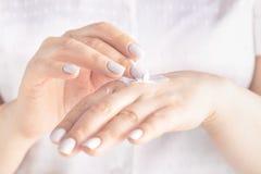 Ενήλικα χέρια γυναικών που εφαρμόζουν την ενυδατική κρέμα στο δέρμα της στοκ εικόνες