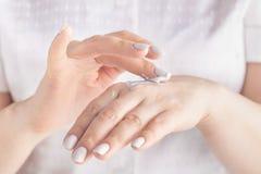 Ενήλικα χέρια γυναικών που εφαρμόζουν την ενυδατική κρέμα στο δέρμα της στοκ φωτογραφία με δικαίωμα ελεύθερης χρήσης