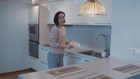Ενήλικη γυναίκα που κατασκευάζει το μικρό κέικ γενεθλίων στη φωτεινή κουζίνα απόθεμα βίντεο