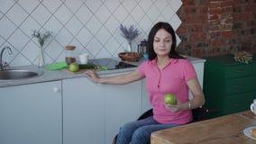 Ενήλικη γυναίκα στην αναπηρική καρέκλα που καθαρίζει το φρέσκο μήλο στην κουζίνα απόθεμα βίντεο