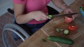 Ενήλικη γυναίκα στην αναπηρική καρέκλα τέμνουσα ντομάτα για τη σαλάτα στο kitche της απόθεμα βίντεο