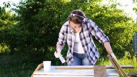 Ενήλικη γυναίκα τεχνών που χρωματίζει τις ξύλινες σανίδες με το άσπρο χρώμα στο θερινό οπωρώνα απόθεμα βίντεο