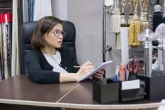 Ενήλικη επιχειρηματίας στον εργασιακό χώρο σχεδιαστής γυναικών, που φορά τα γυαλιά, τις εργασίες με τον υπολογιστή και τα δείγματ στοκ φωτογραφία με δικαίωμα ελεύθερης χρήσης