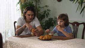 Ενήλικη και μικρή συνεδρίαση αγοριών δύο αδελφών στον πίνακα κουζινών, ομιλία και κατανάλωση croissant με το cappuccino brow φιλμ μικρού μήκους