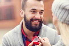 Ενήλικος άνδρας που δίνει το δαχτυλίδι αρραβώνων στην όμορφη γυναίκα Στοκ Εικόνα