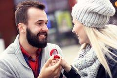 Ενήλικος άνδρας που δίνει το δαχτυλίδι αρραβώνων στην όμορφη γυναίκα Στοκ εικόνα με δικαίωμα ελεύθερης χρήσης