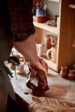 Ενήλικος αρσενικός κύριος αγγειοπλαστών που διαμορφώνει το πιάτο αργίλου σύμφωνα με τη ρόδα αγγειοπλαστών ` s Τοπ άποψη, κινηματο Στοκ Εικόνα