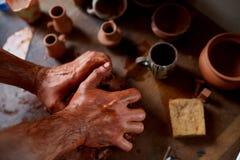 Ενήλικος αρσενικός κύριος αγγειοπλαστών που διαμορφώνει το πιάτο αργίλου σύμφωνα με τη ρόδα αγγειοπλαστών ` s Τοπ άποψη, κινηματο Στοκ Εικόνες