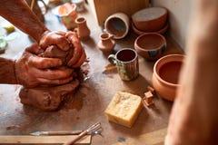 Ενήλικος αρσενικός κύριος αγγειοπλαστών που διαμορφώνει το πιάτο αργίλου σύμφωνα με τη ρόδα αγγειοπλαστών ` s Τοπ άποψη, κινηματο Στοκ Φωτογραφίες