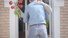 Ενήλικος εγγονός που επισκέπτεται τη γιαγιά του, που φέρνει την ανθοδέσμη τουλιπών της Το γενειοφόρο άτομο που αγκαλιάζει τη γιαγ απόθεμα βίντεο
