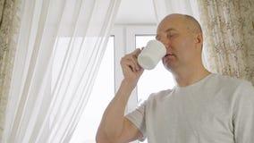 Ενήλικος καφές πρωινού κατανάλωσης ατόμων στην άνετη κουζίνα στο υπόβαθρο παραθύρων Εύθυμο άτομο πορτρέτου που απολαμβάνει το καυ απόθεμα βίντεο